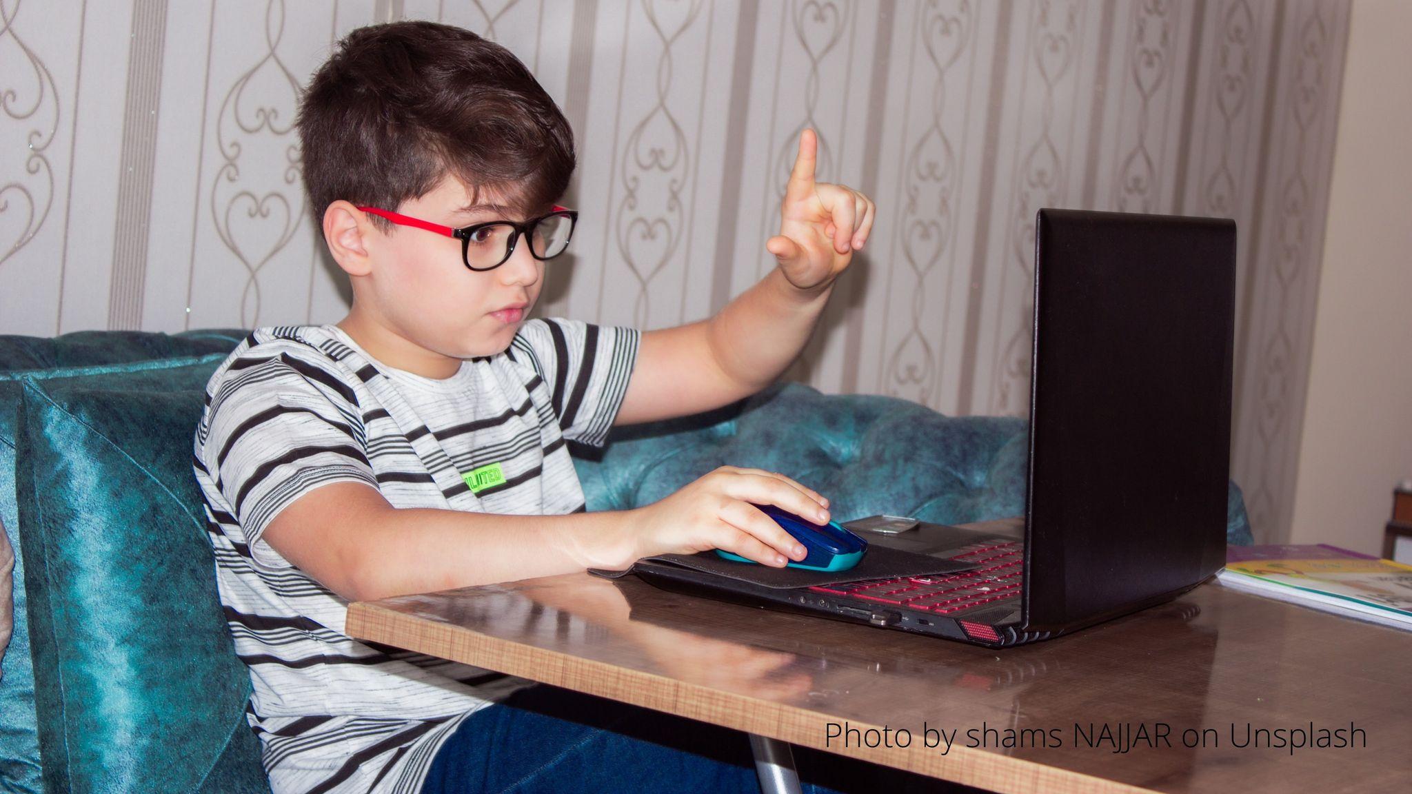 Zdjęcie przedstawia chłopca siedzącego przed komputerem.